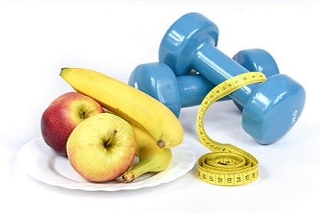 Apples and bananas on a plate with blue dumbbells and a yellow tape measure